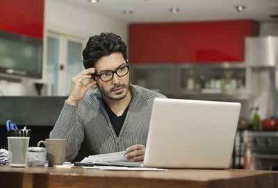 A homeowner looks over his homeowners insurance policy.