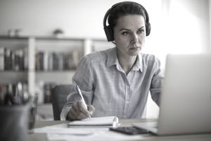 Woman on computer with headphones taking notes