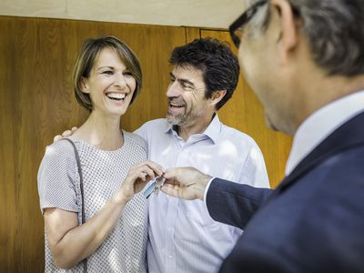 Man handing keys over to a smiling couple