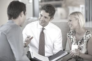 Financial advisor talking to couple on sofa
