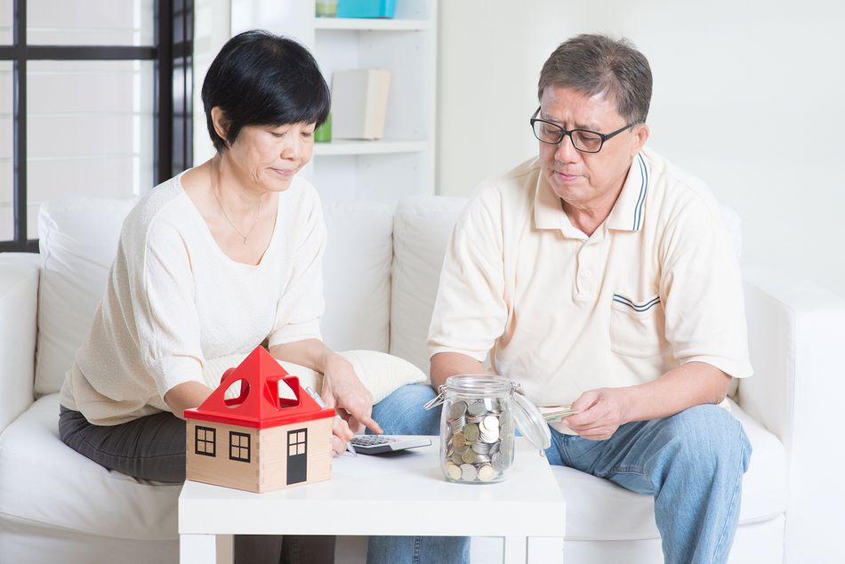 Couple seated on a sofa with a calculator and a jar of change on the table next to a cardboard figure of a house