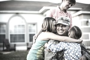 Mother watching over two daughters hugging their dad, who wears military fatigues in the front yard of their house