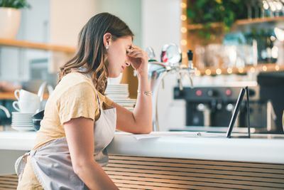 Frustrated coffee shop owner thinking at counter