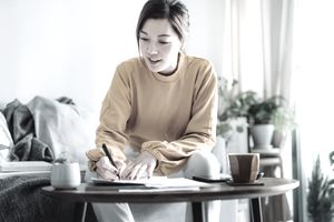 Person signing a document while sitting at a coffee table