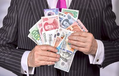 International banker holds a mix of different countries' currencies
