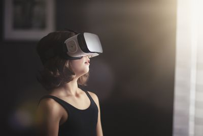 A young girl wears virtual reality goggles.