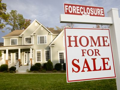A house with foreclosure for sale sign in the front yard