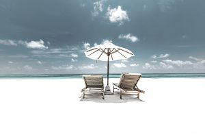 Two lounge chairs on a beach at a honeymoon resort