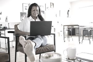 Barefoot creative businesswoman using laptop in home office