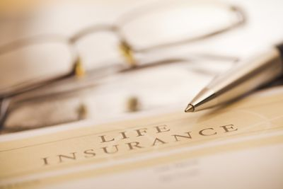 Whole life insurance policy form with a pen and eyeglasses