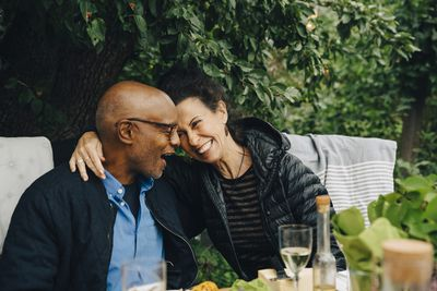 A retired couple sits in their backyard enjoying a glass of wine together.