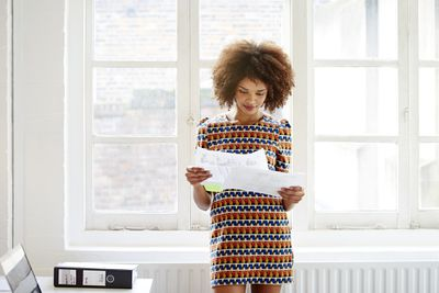 Young woman looks over her credit card statement