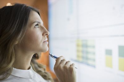 Close up focused businesswoman looking up projection screen