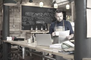 Coffee shop owner reviewing bank statements at a cafe table