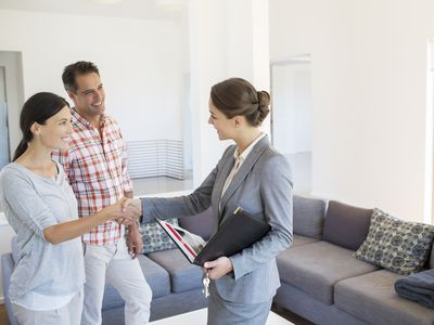 a businesswoman and a couple shaking hands in a living room