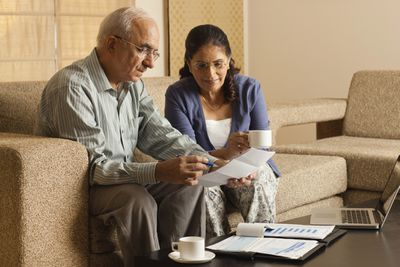 Senior couple working in living room, with laptop on coffee table