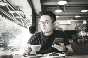 A young man sits at a cafe table and stres out the window to his right. He holds a cup of tea in his right hand and a smartphone in his left.