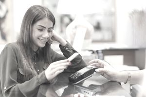 A young woman uses a contactless card on her phone to pay for a purchase at a store