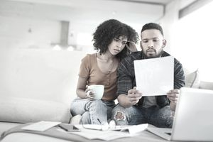 Couple looking distressed while reviewing insurance bills