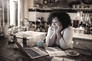 Woman Smiles as She Looks at Her Laptop