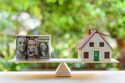 A balance beam with rolls of money counterbalanced by a home representing a reverse mortgage.