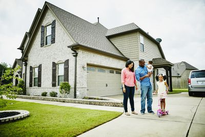 A family stands on the driveway in front of a recently built home.