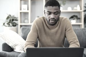 man sitting in yellow sweater on grey couch in front of computer