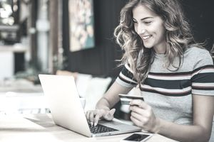 Young woman looking happily at laptop.