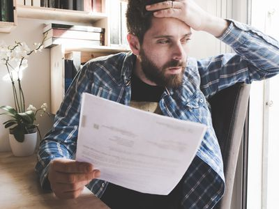 Worried man sitting in a chair with his hand on his head, reading a car insurance cancellation letter.