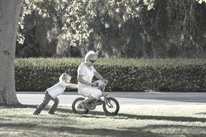 senior on bike pushed by child.jpg
