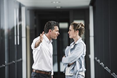 A man and a woman stand face to face in a business setting.