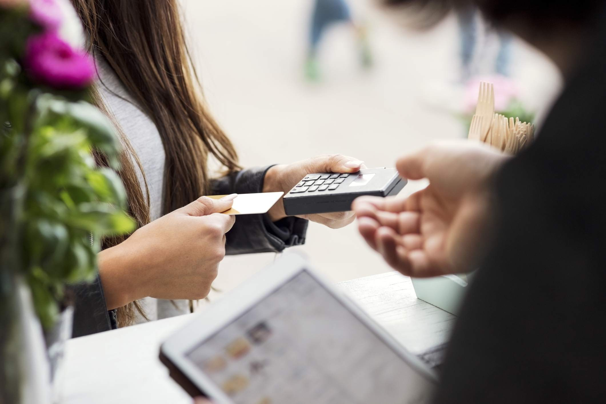 Woman inserting credit card to card reader at point of sale