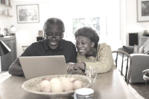 Senior couple using laptop at dining table