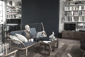A homeowner sits on a couch while looking at a laptop