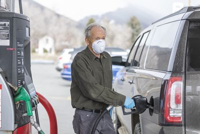 Man wearing surgical gloves and mask refueling car at gas station.