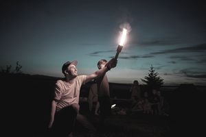 A young man holds a lit firework shooting flames into the sky while child watches.