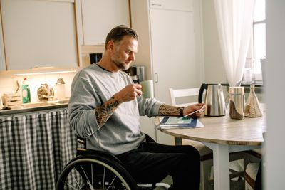 Tattooed mature man reading mail while holding coffee cup on wheelchair at home