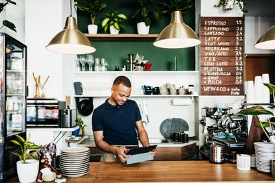 Business owner using tablet in coffee shop