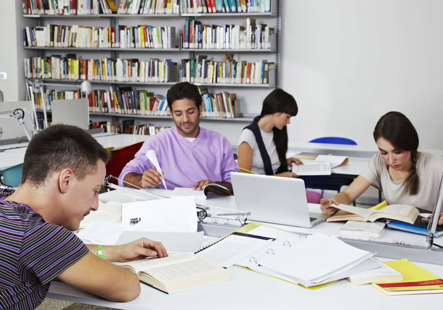 College students studying at library tables with open books and binders scattered around them