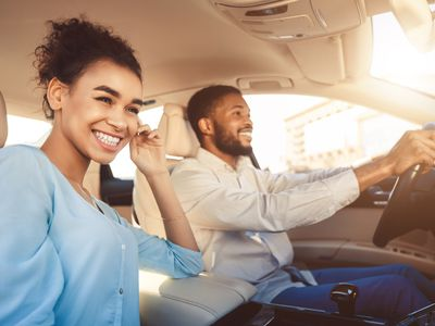 A young couple smiling as the check out a new car's interior in a dealers showroom