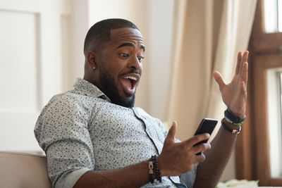 A surprised man looks at his phone in shock and happiness