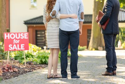 Back view of hugging couple with realtor in the driveway of a home they may buy that is for sale