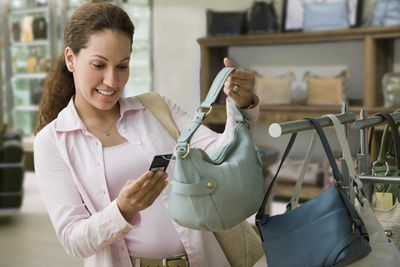 A customer in a store checks the price tag of a purse.