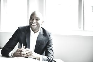 Smiling businessman in discussion at workstation - stock photo
