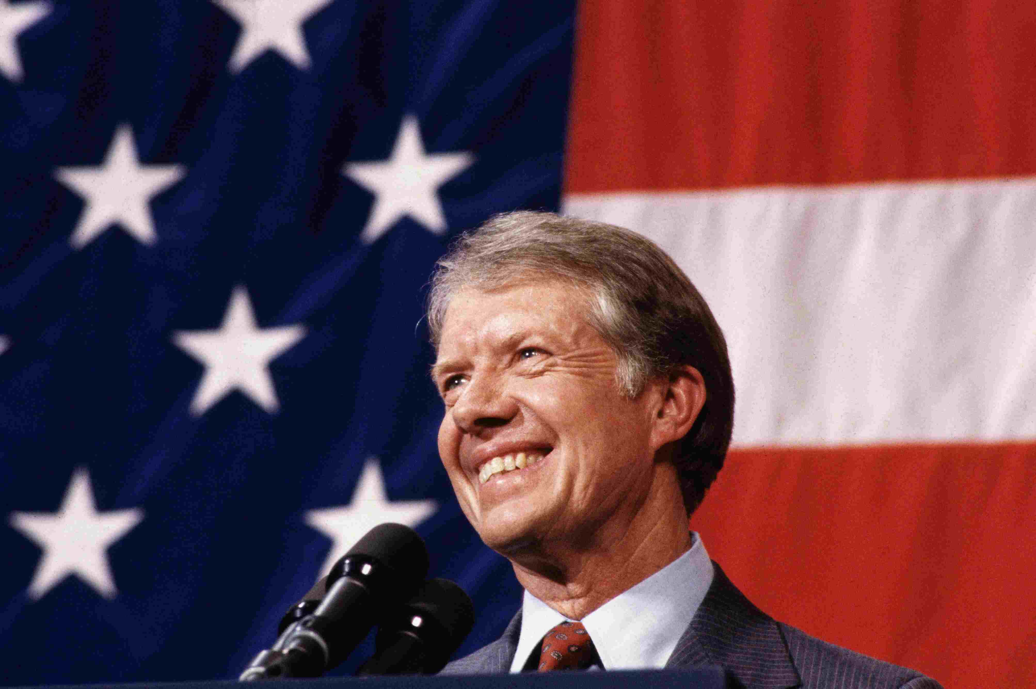 President Jimmy Carter giving a speech with an American flag backdrop