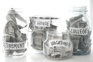 """Four glass jars labeled with financial goals and labeled """"Retirement,"""" """"House,"""" Vacation,"""" and """"College."""""""