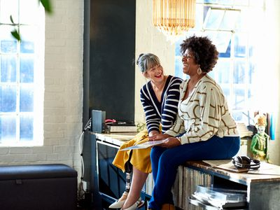 Two mature women laughing sitting on countertop of bright lobby