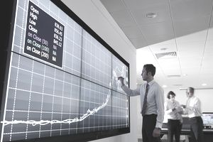 A man charting data on a video wall