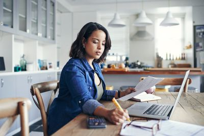 A woman sits at a kitchen table and works on her bills with a calculator and an open laptop.