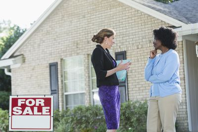 A real estate agent stands in front of a house with a for sale sign, talking with another woman